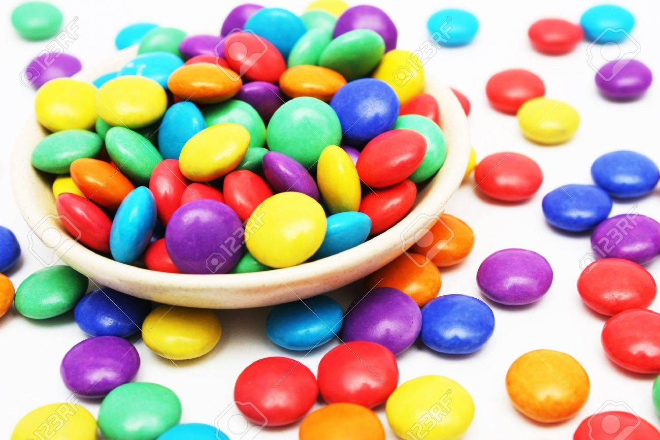 A lot of colorful candies on small dish and some scattered around it. - 3098806