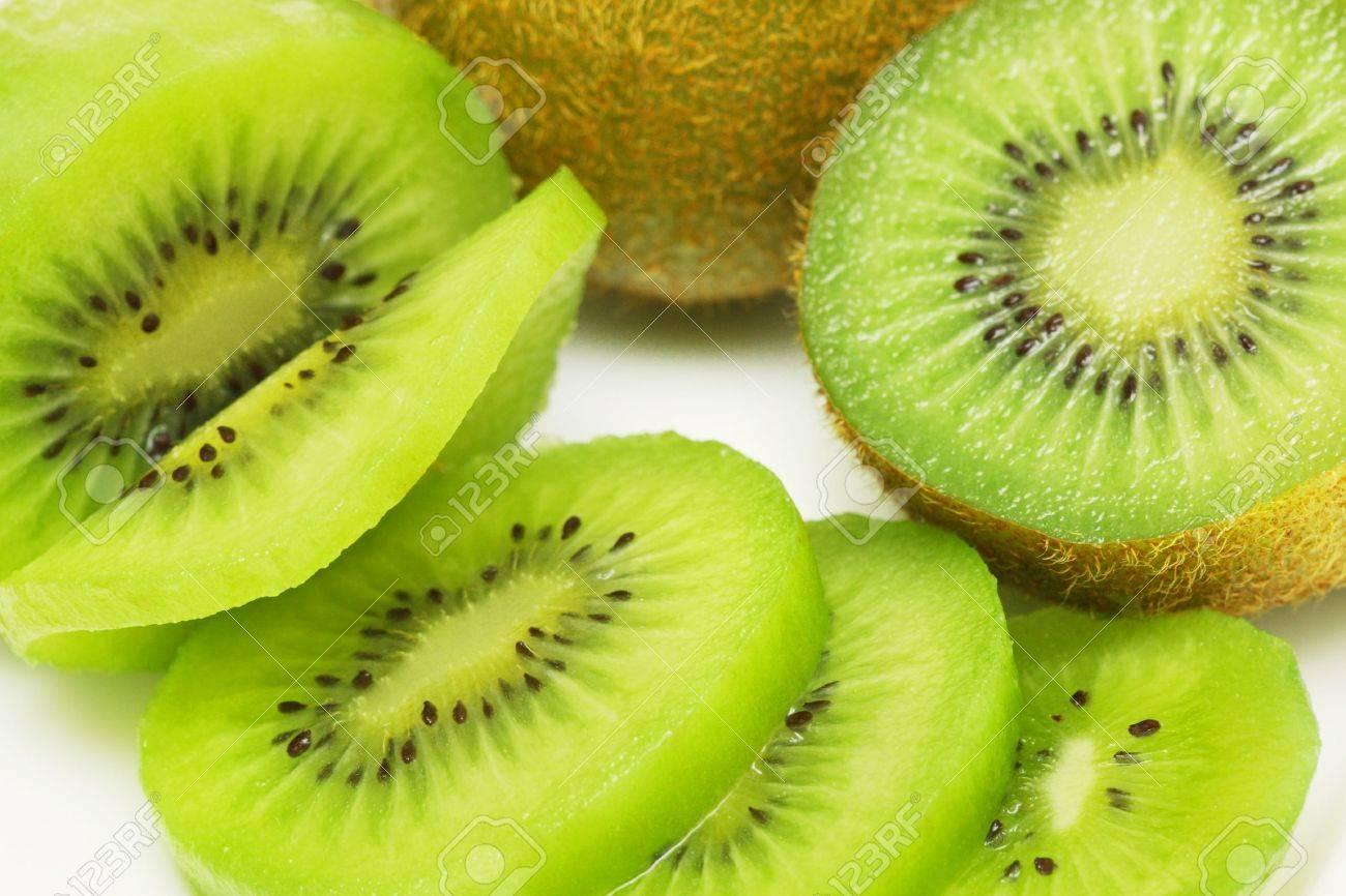 Kiwi fruit sliced into pieces on white background. - 3485562
