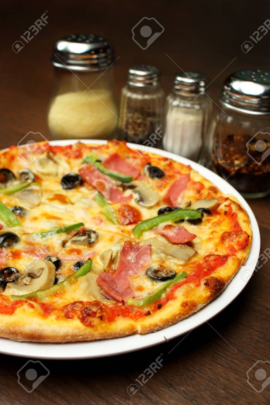 Close up of a pizza with seasoning on brown table. - 4627796
