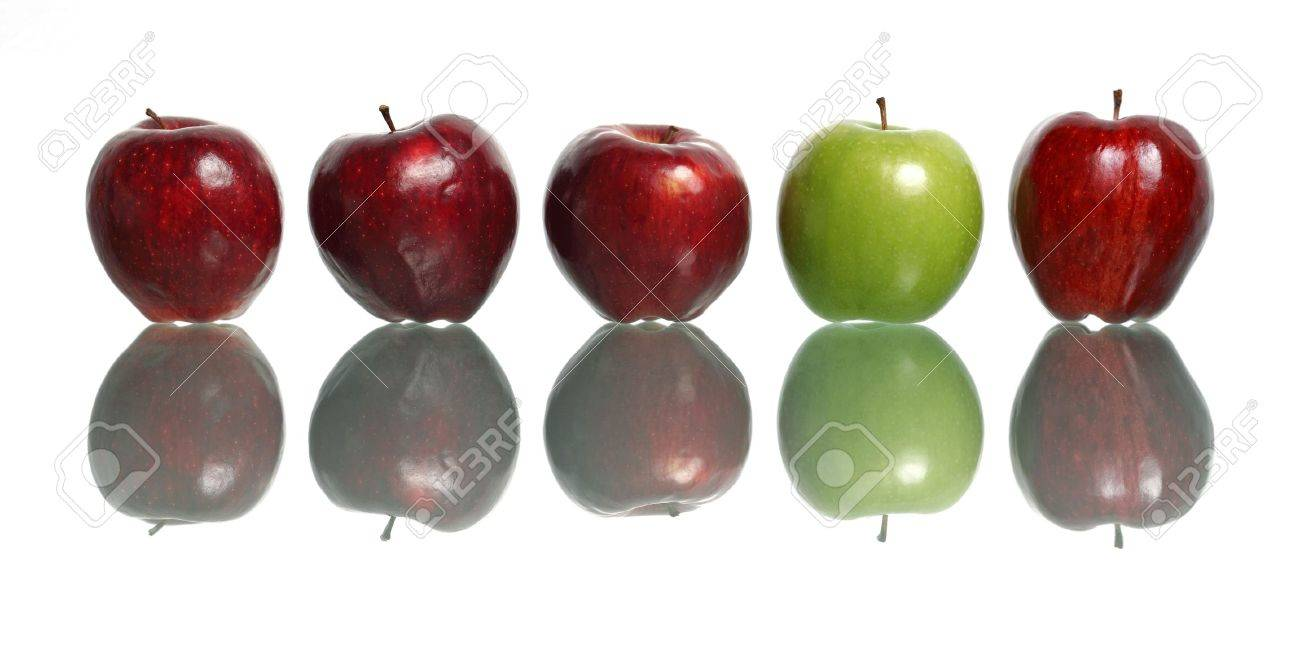 A green apple being standout among red apples isolated on white background. - 10079203