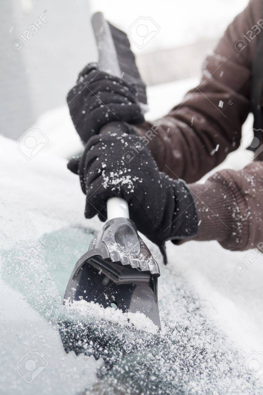 scraping snow and ice from the car windscreen - 8424694