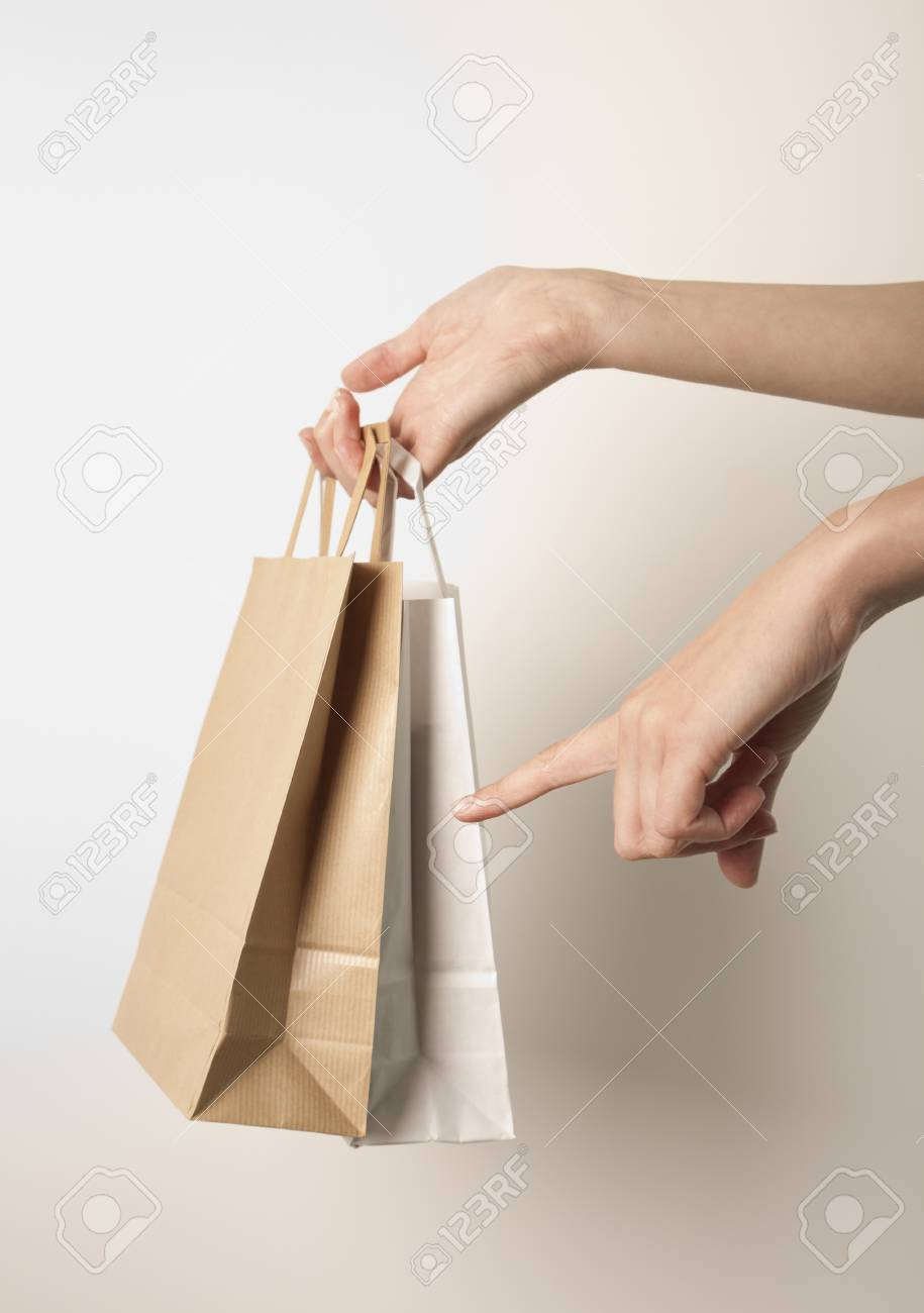 Holding paper bags. Consumerism symbol. Stock Photo - 14408800
