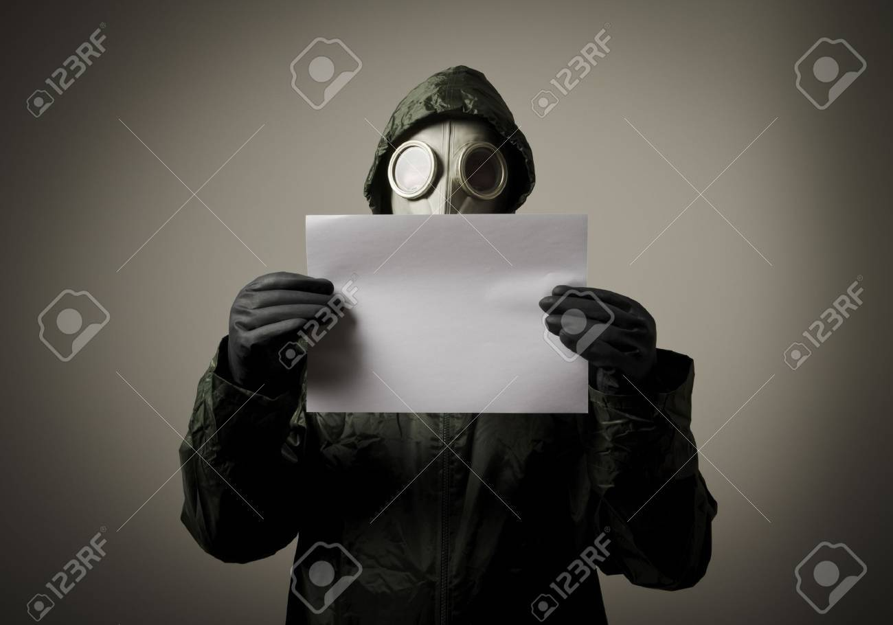 Man wearing a gas mask on his face and holding white paper - 21656263