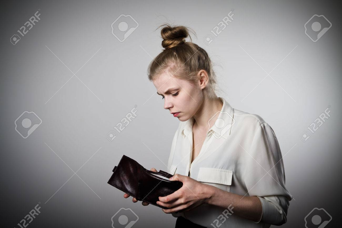 Worried slim woman is looking at an empty wallet - 56556135