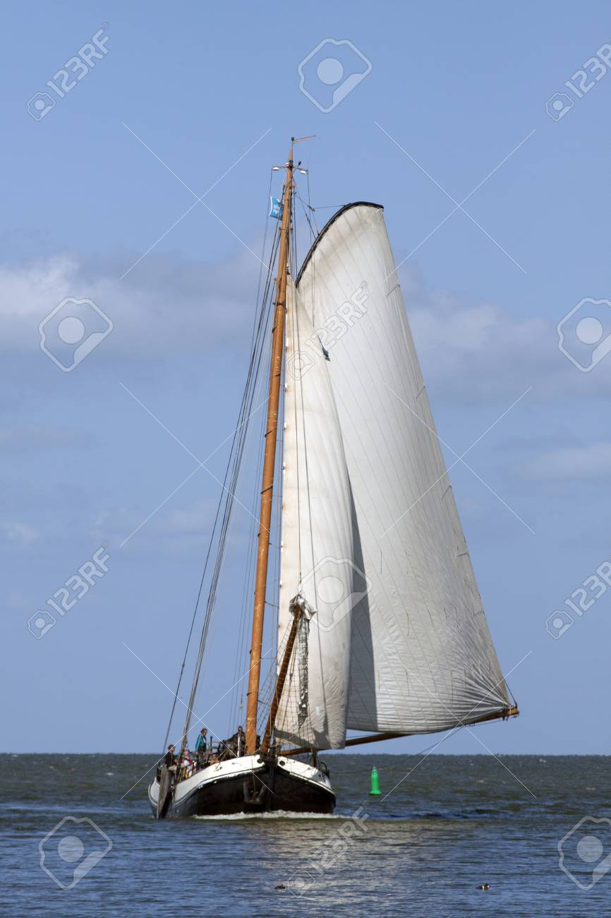 Old Wooden Sailing Boat With White Sails Hoisted