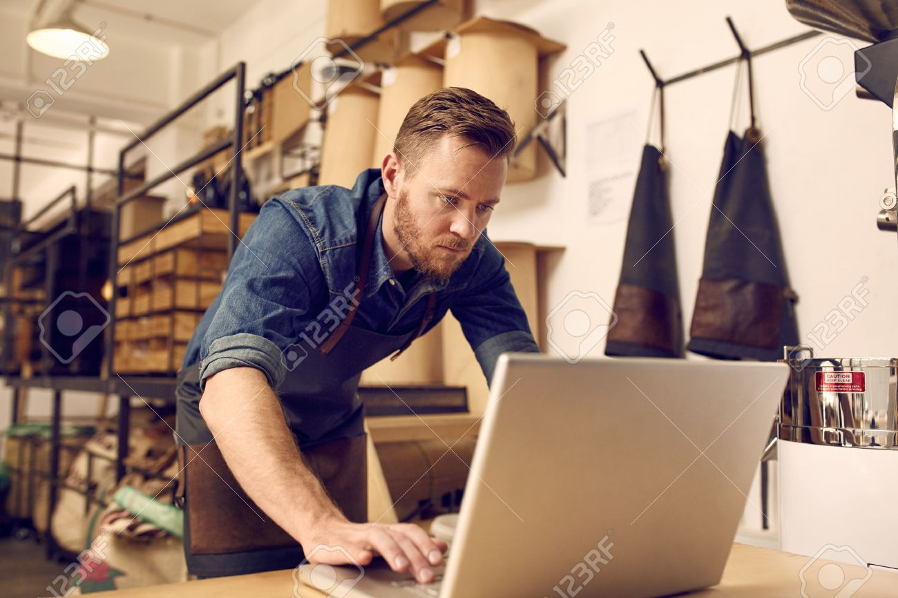 Handsome young male business owner looking serious while working on his laptop with a neat and tidy workshop behind him Stock Photo - 51441469