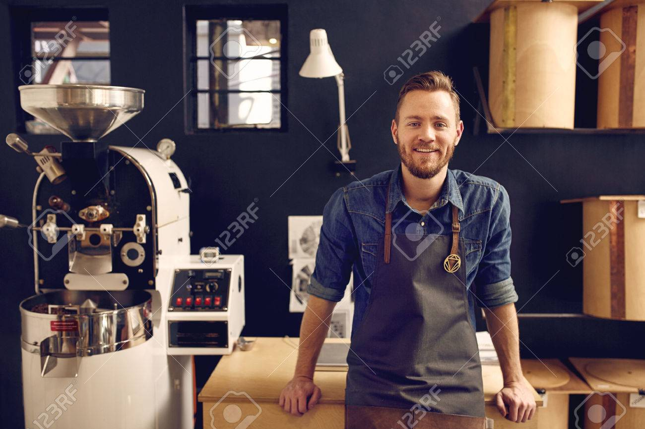 Portrait of a smiling man looking relaxed and confident in his workspace where he roasts coffee beans and distributes them - 51441887