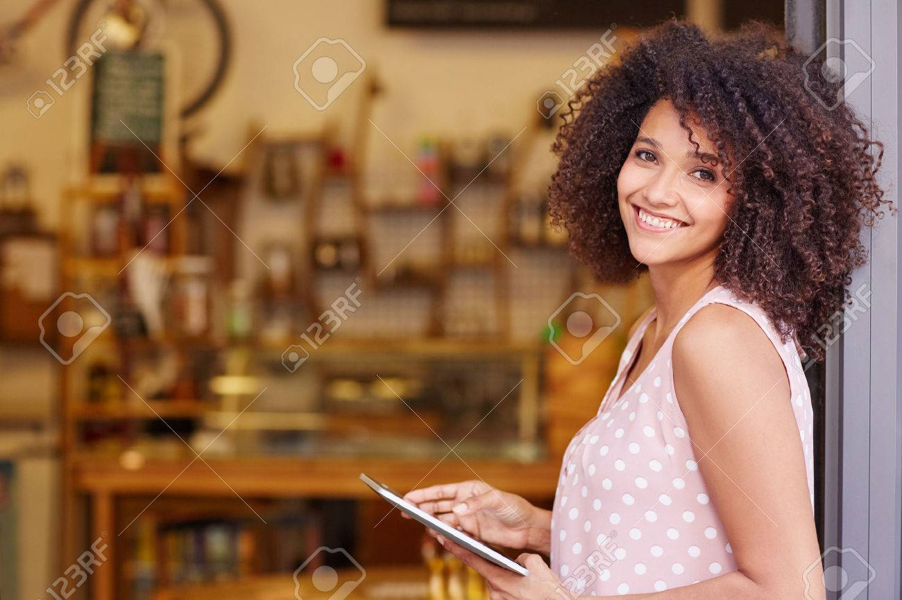 Beautiful mixed race woman with an afro hairstyle holding a digital tablet while standing in the doorway of her coffee shop - 51356857