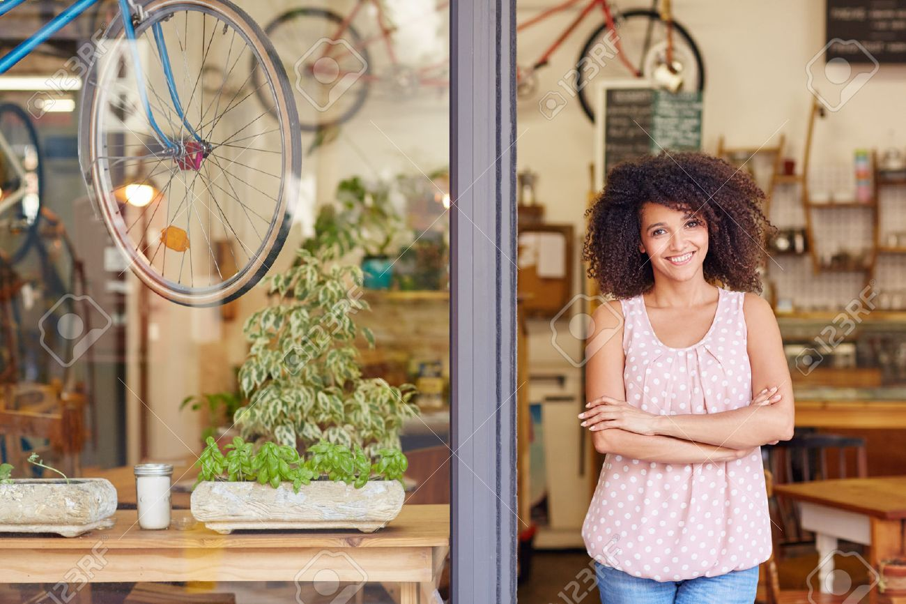 Young mixed race woman smiling, while standing in the door of her cafe with her arms folded proud to be the owner of a small business Stock Photo - 51356645