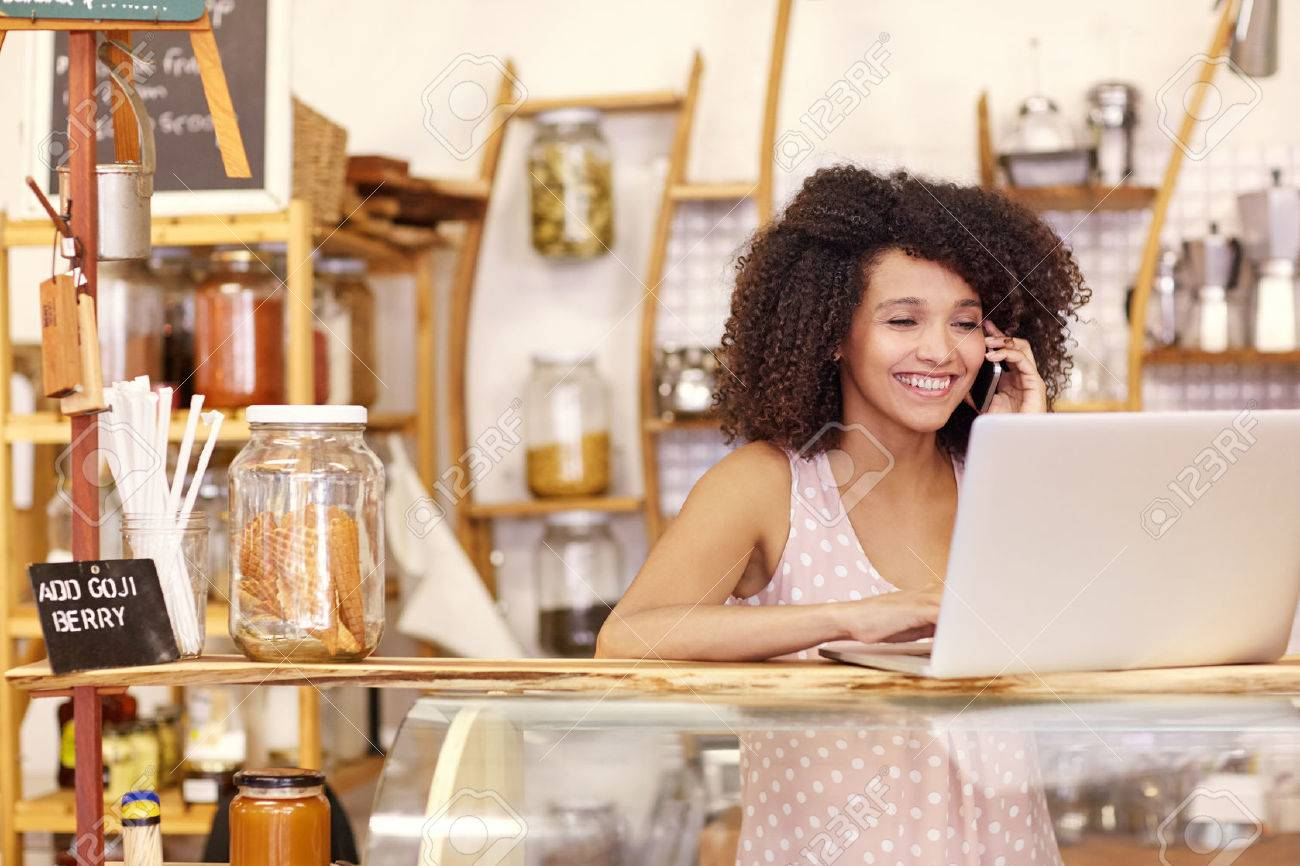 Happy young coffee shop owner talking on he mobile phone while typing on her laptop on the counter - 51356657