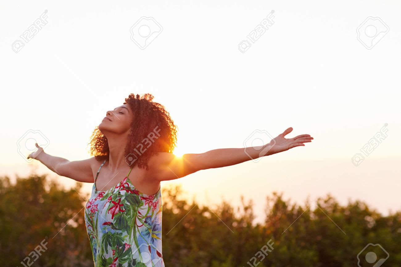 Beautiful mixed race woman expressing freedom outdoors with her arms outstretched - 51356326