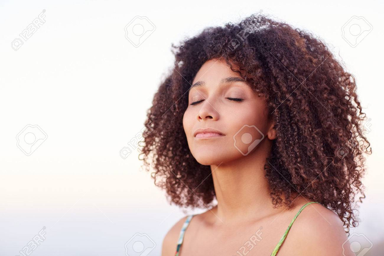 Beautiful mixed race woman with her eyes closed outdoors in a serene moment - 51355978