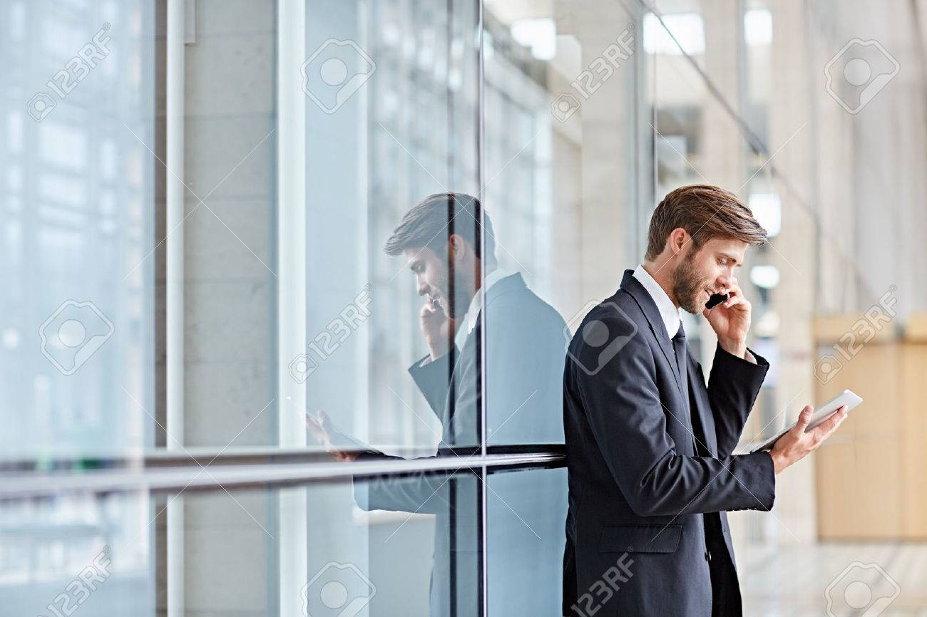 Corporate executive smiling while talking on his phone and looking at a digital tablet - 51813595