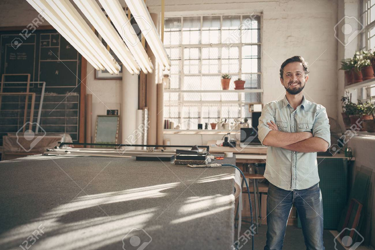 Portrait of a good looking male designer standing in his workshop studio with his arms folded and smiling confidently at the camera Stock Photo - 51813662