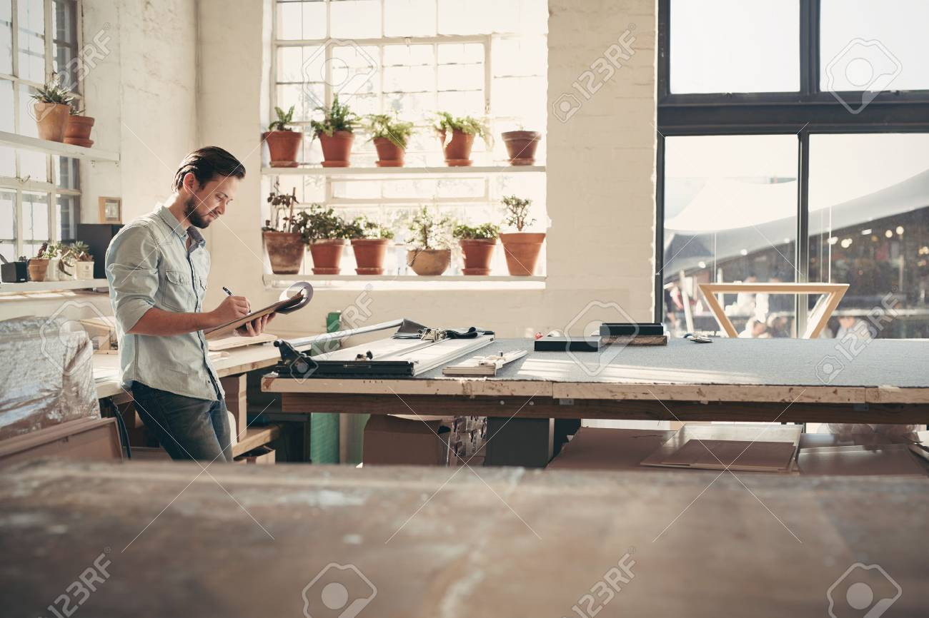 Young male business owner standing in his studio workshop checking figures and stock on his clipboard on a sunny afternoon - 51813672