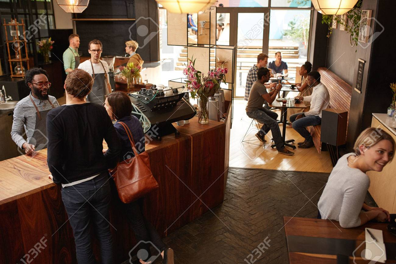 High angle shot of a couple ordering at a wooden counter in a modern coffee shop with a hipster style - 53614595