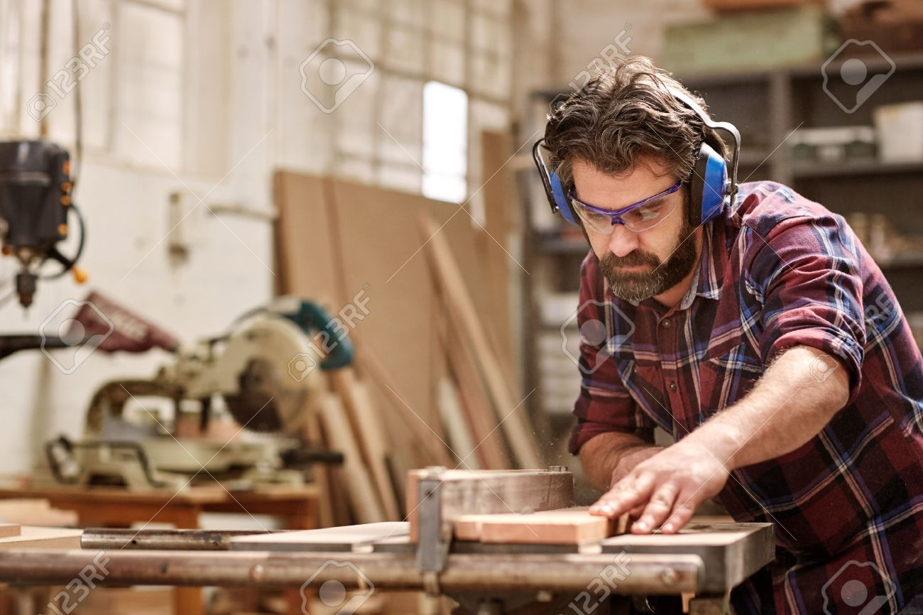 Skilled carpenter cutting a piece of wood in his woodwork workshop, using a circular saw, and wearing safety googles and earmuffs, with other machinery in the background - 54601230