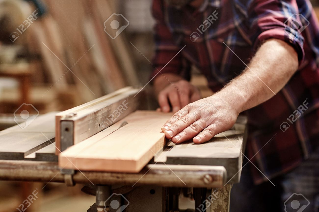 Cropped image of the hands of a skilled craftsman cutting a wooden plank with a circular saw in a workshop - 54601237