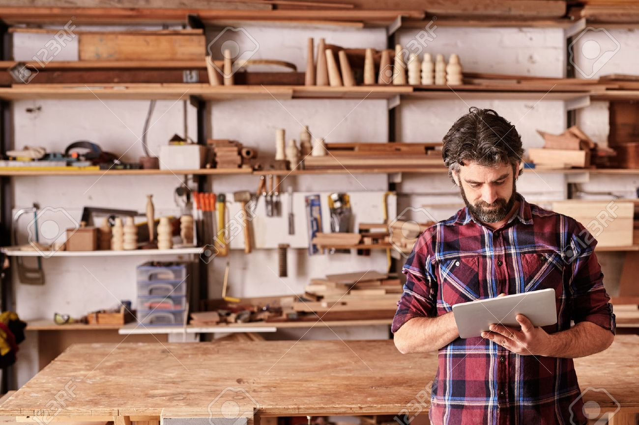 Artisan woodwork studio with shelving holding pieces of wood, with a carpenter standing in his workshop using a digital tablet Stock Photo - 54641903