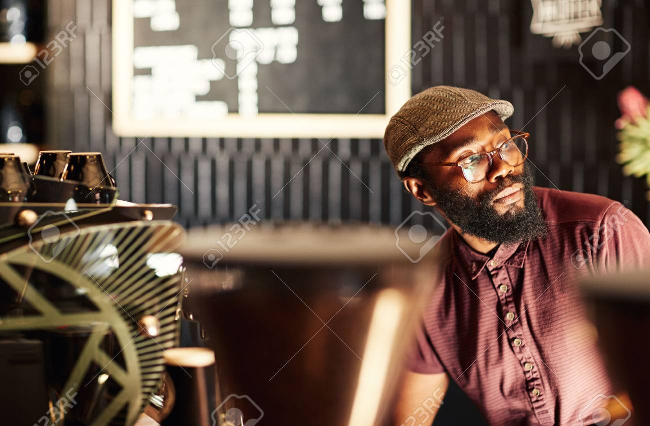 Portrait of a fashionable African man with a hipster style beard, spectacles and cap, sitting in a modern coffee shop and looking away in deep thought, with gentle light falling on his face Standard-Bild - 54728198