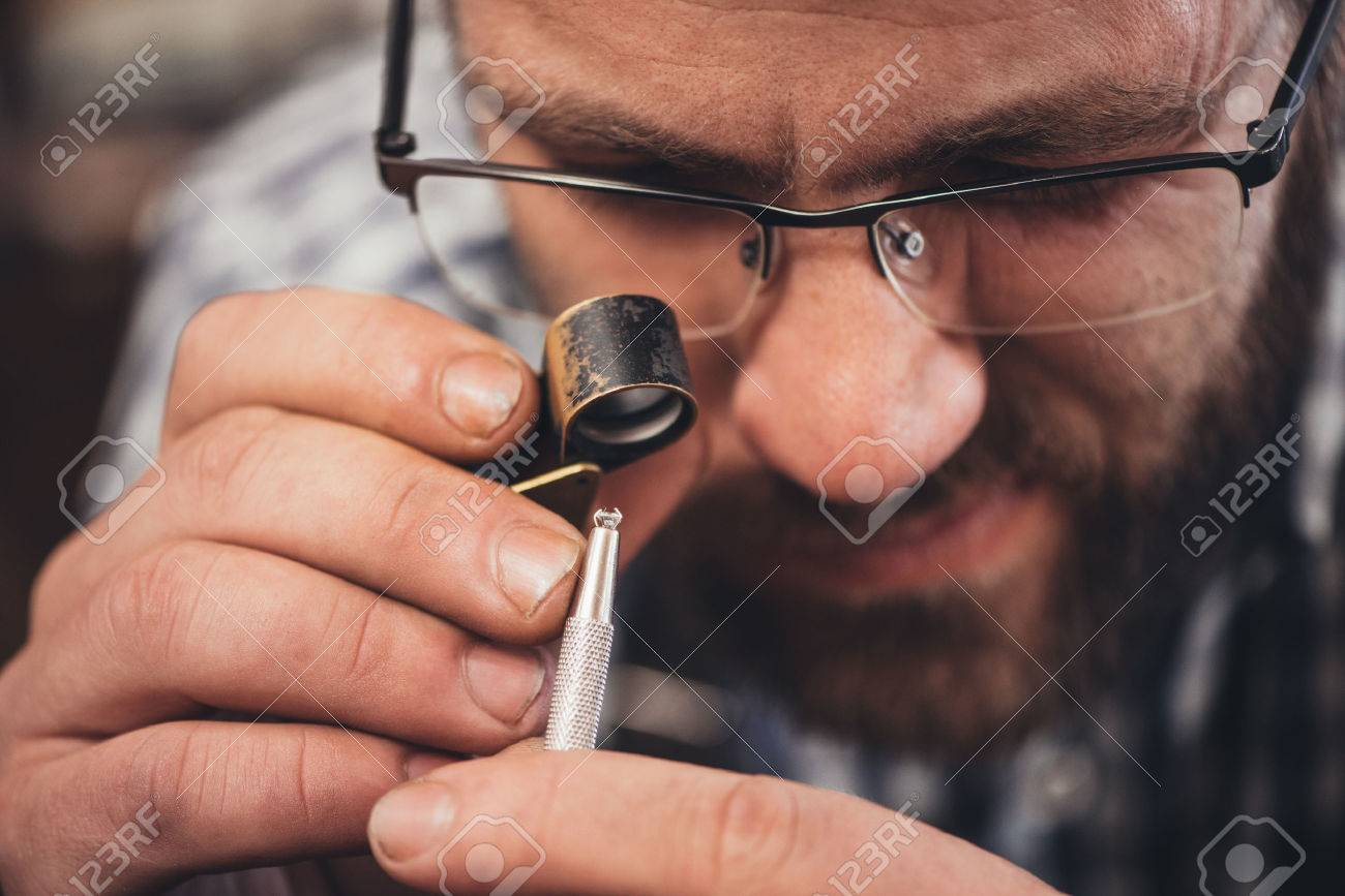 Closeup Of A Jeweler Using A Loupe To Examine A Diamond He Is ...