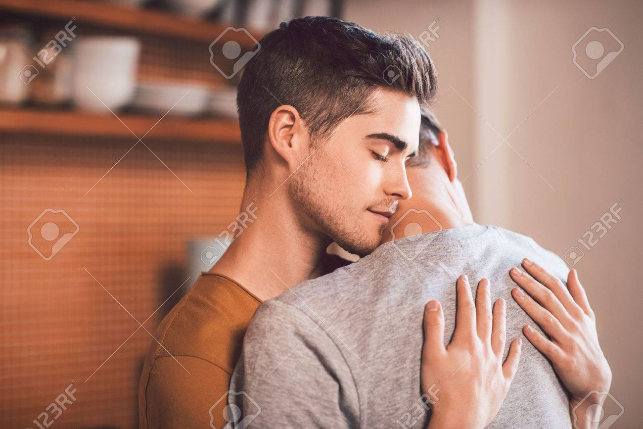 Affectionate Young Gay Couple Hugging Each Other With Their Eyes Closed While Standing In Their Kitchen