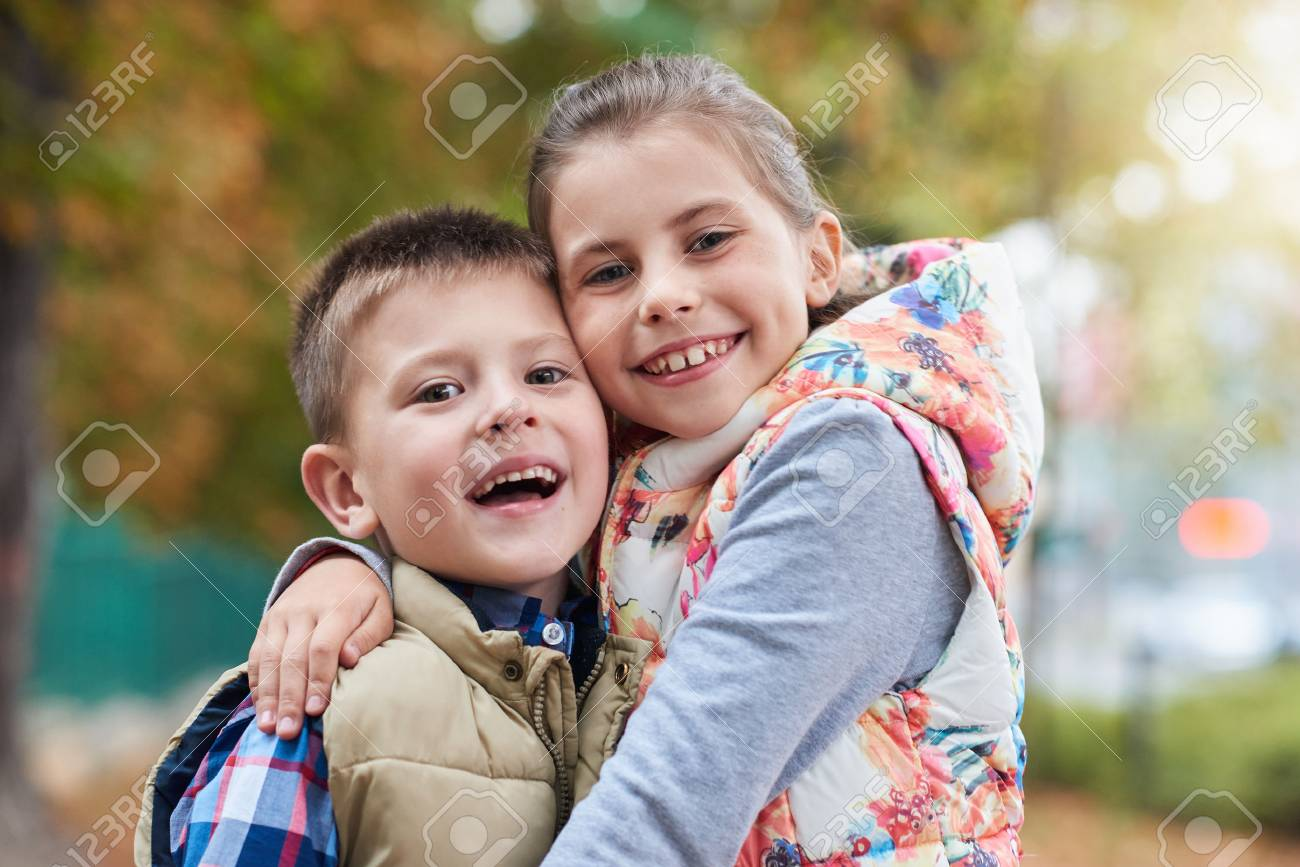 happy siblings hugging outside stock photo picture and royalty free