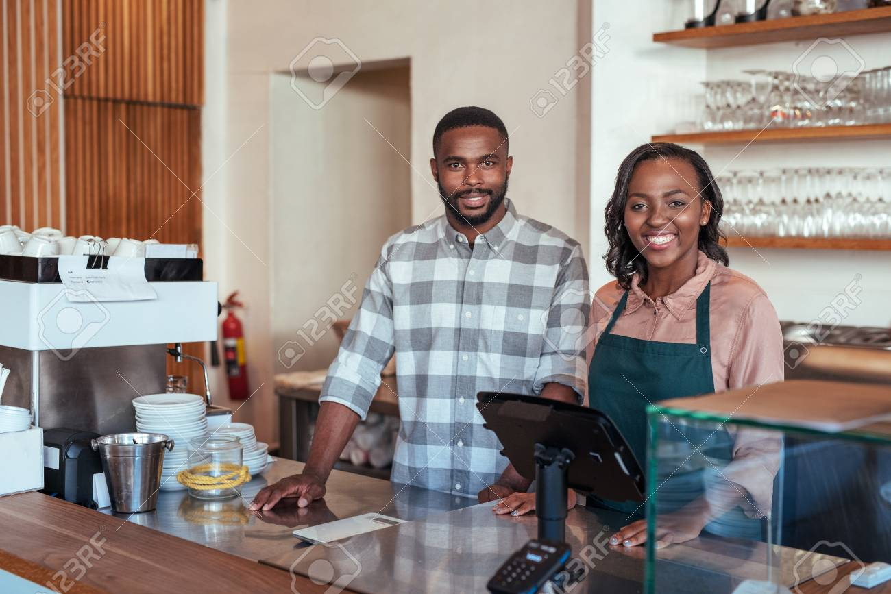 Smiling African entrepreneurs standing at the counter of their bakery - 89828765