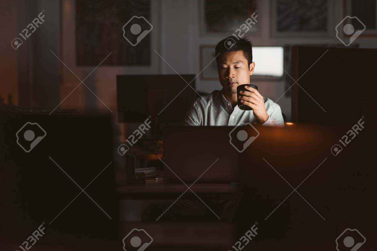 Asian businessman drinking coffee while working late in an offic - 108839402