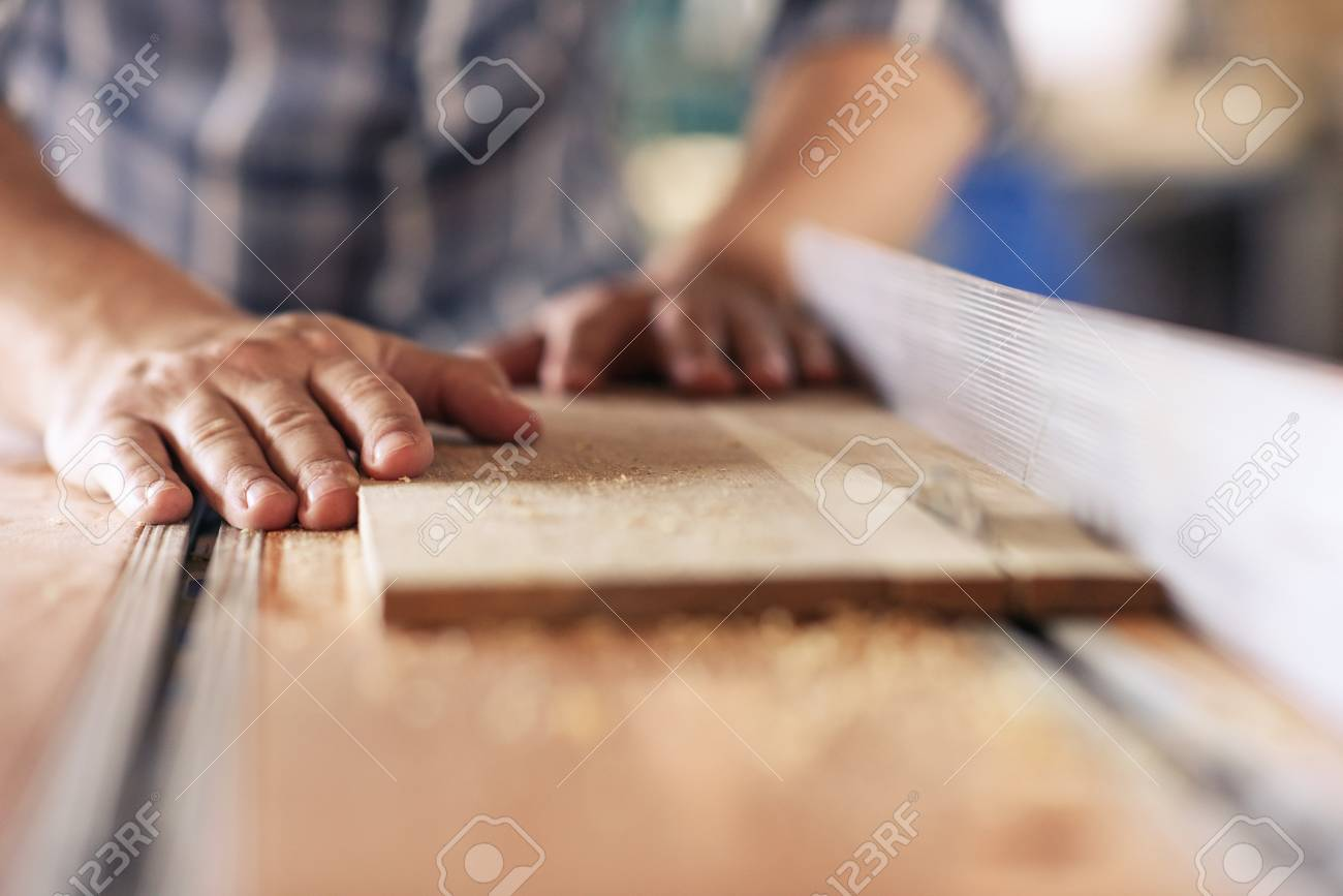 Woodworker sawing planks of wood in his carpentry workshop - 116616400