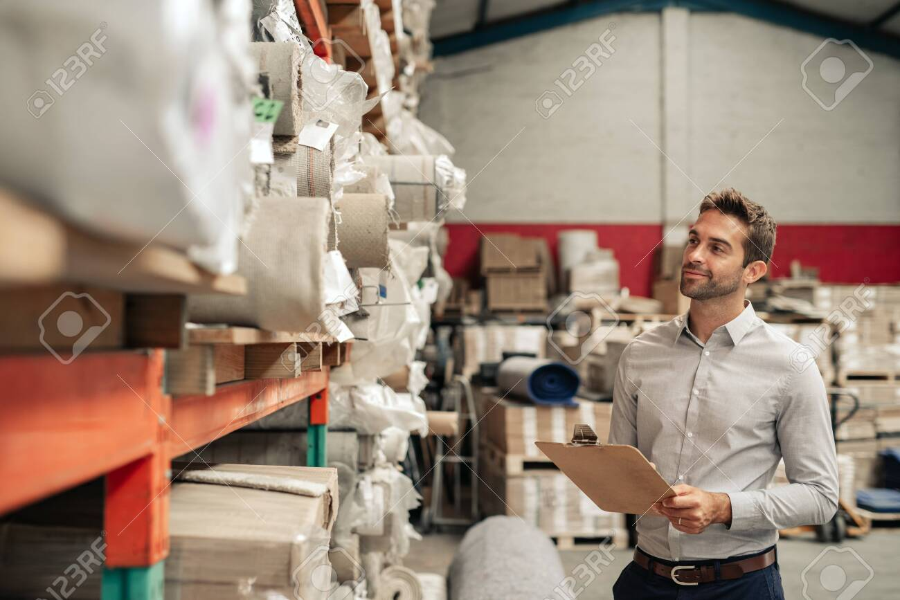 Smiling warehouse manager using a clipboard while doing inventory - 123714636