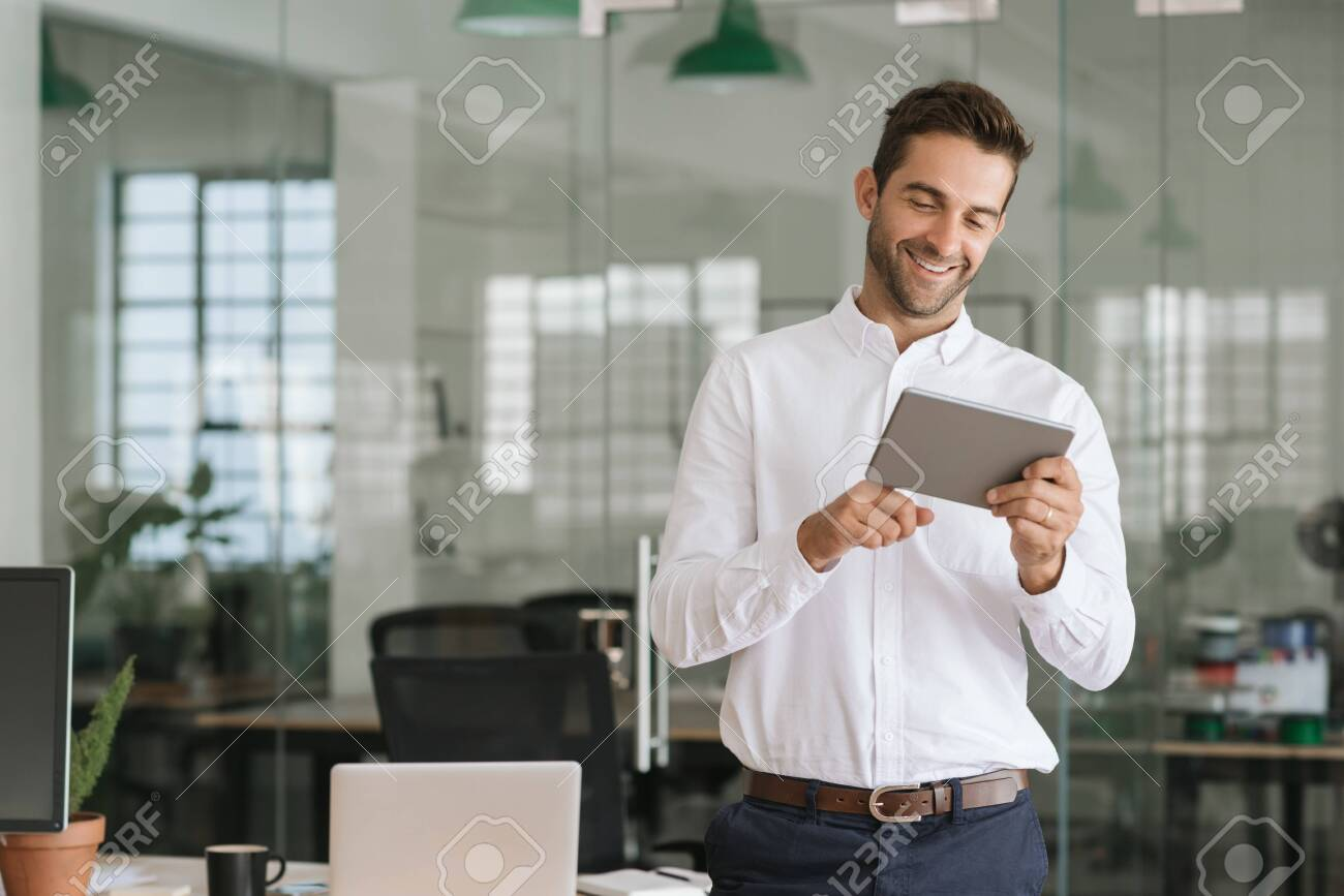 Smiling businessman using a tablet in a large modern office - 127417637