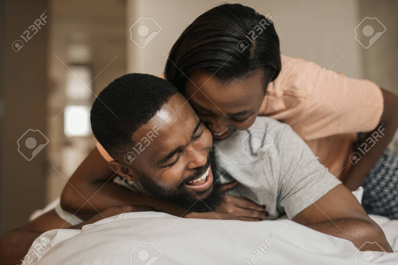 Laughing young African American couple playing in bed together - 130068271