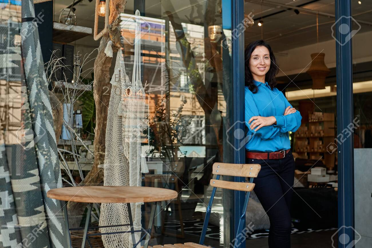 Smiling Asian entrepreneur standing at the entrance of her boutique - 147553947
