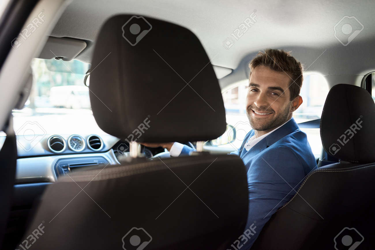 Friendly driver looking over his shoulder and smiling - 155898579