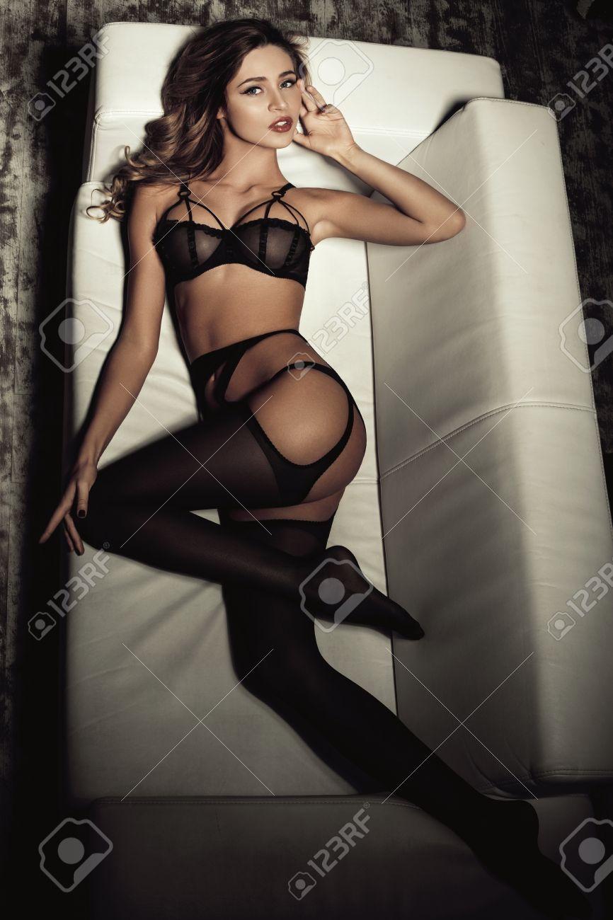 ceb647abbb9eae Sexy Frau in verführerische schwarze Dessous auf einem Sofa liegend in  Strümpfen Standard-Bild -