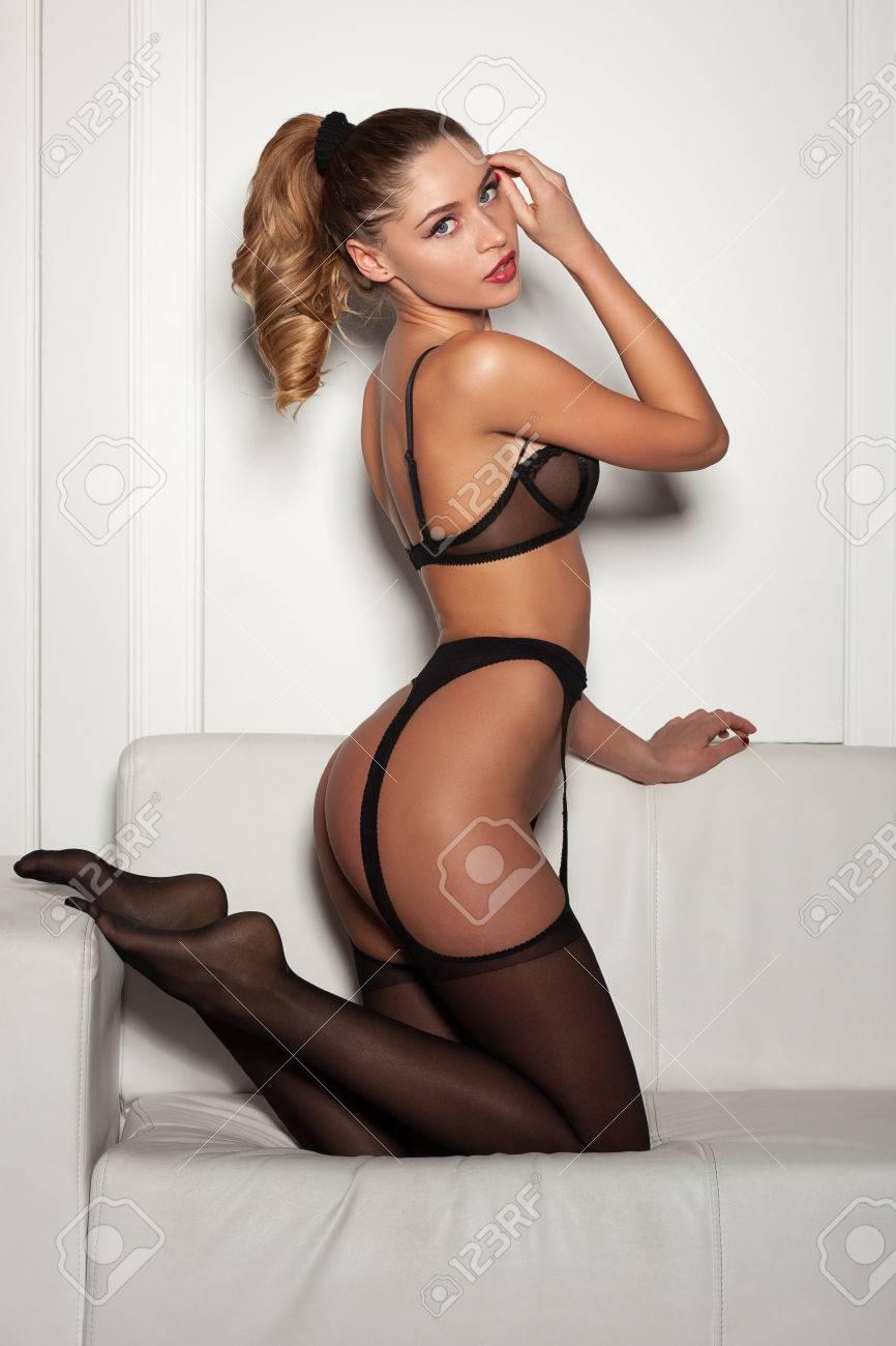 c9c8ab8b3 Foto de archivo - Mujer sexy en ropa interior negro seductora sentada en un  sofá en medias
