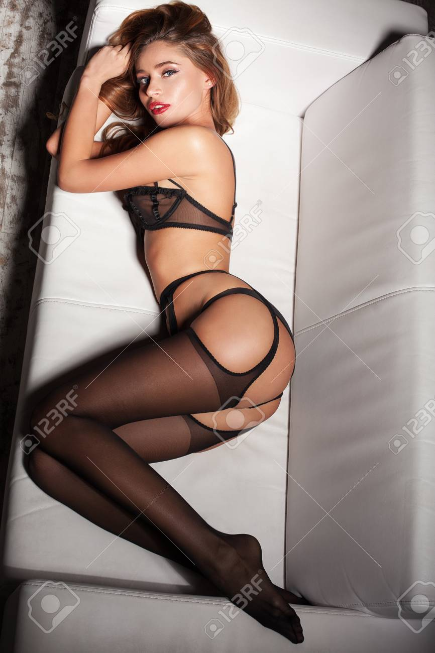 3b2ef3adf Foto de archivo - Mujer sexy en ropa interior negro seductora acostado en  un sofá en medias