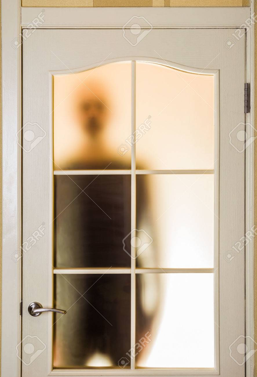 Silhouette Of An Unknown Man In Black Seen Through A Closed Glass Door Like