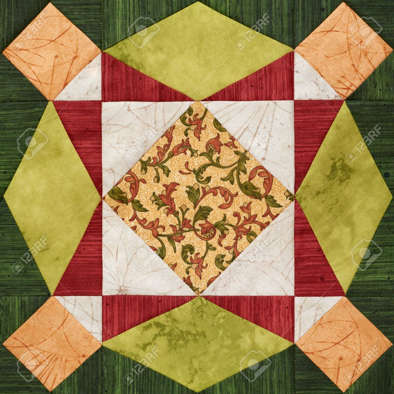 Bright orange green geometric patchwork block from pieces of fabrics detail of quilt stock
