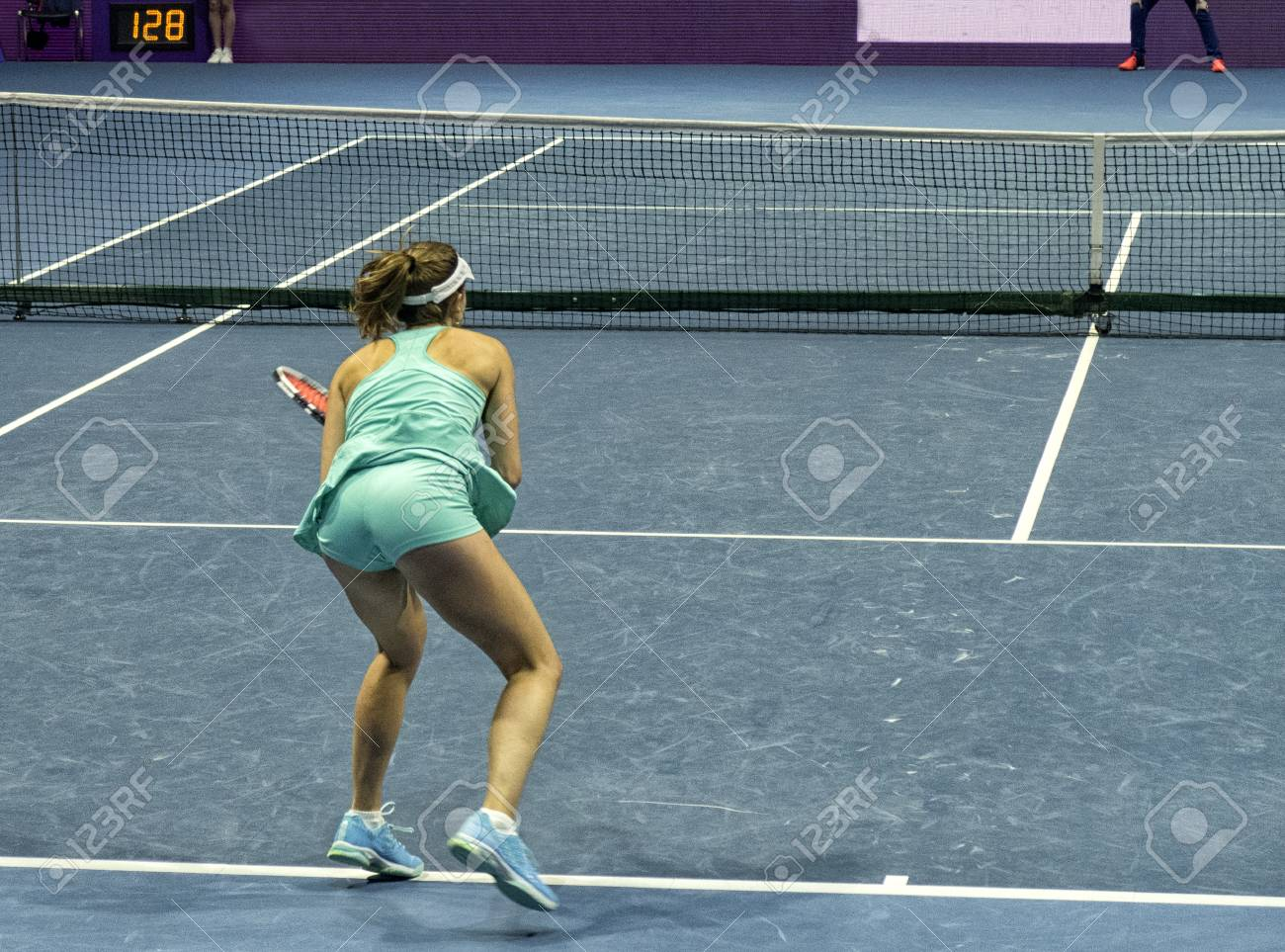 Young Woman Playing Tennis On A Court With An Artificial Surface
