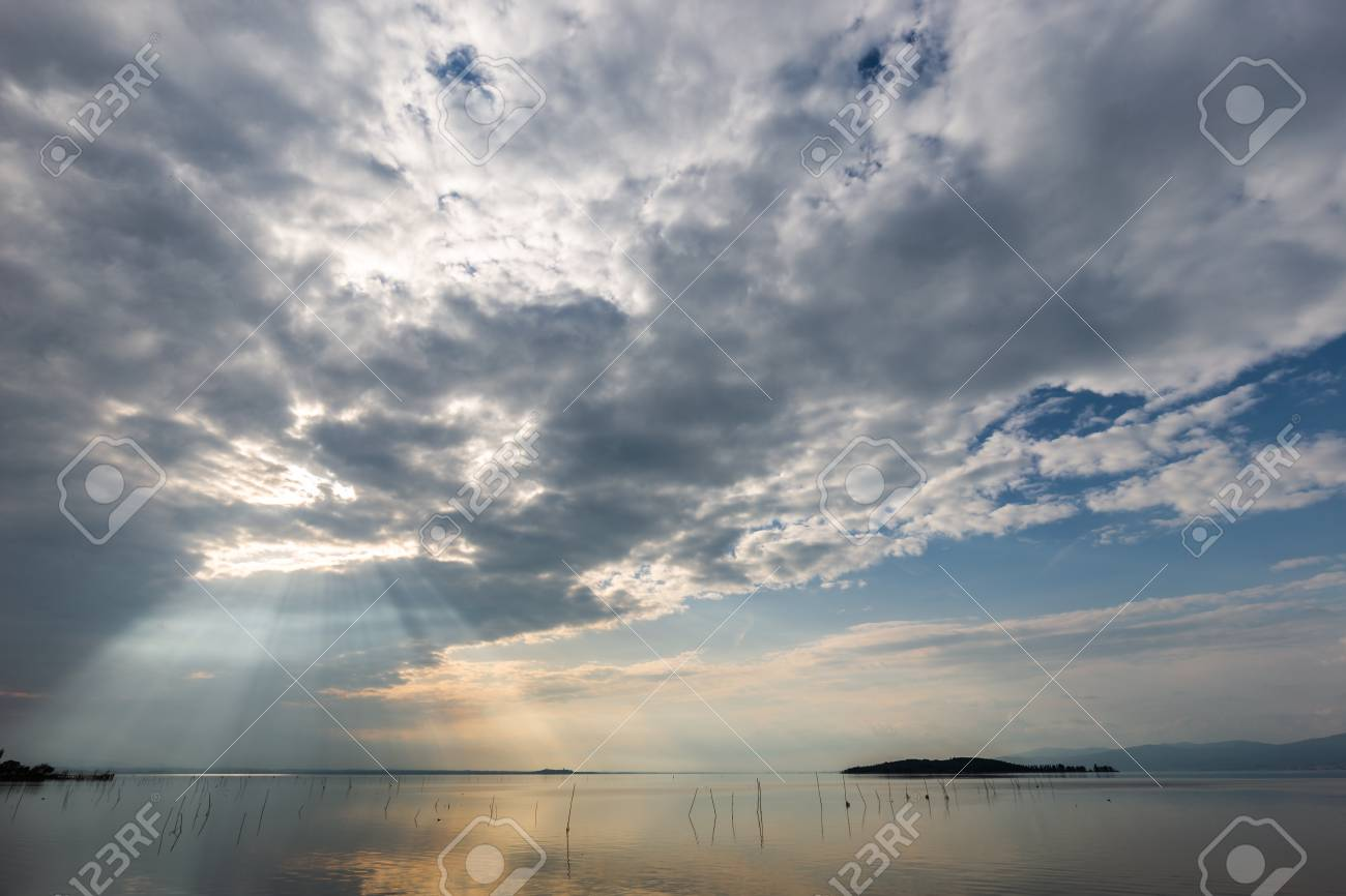 spectacular view of a lake with clouds sky and sun rays reflecting