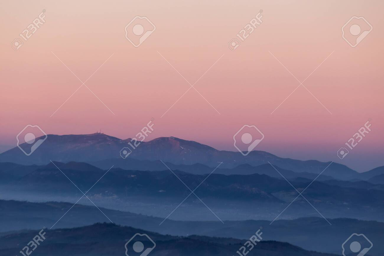 Beautifully colored sky at dusk, with mountains layers and mist between them - 122261164