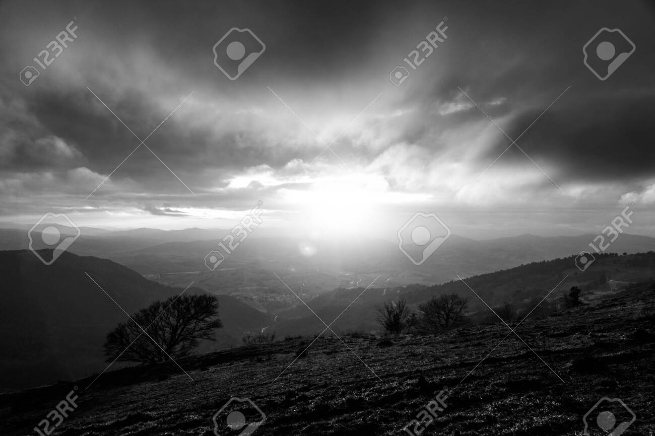 Moody sunset on Monte Cucco (Umbria, Italy), with tree in the foreground and sun filtering through clouds - 131934949