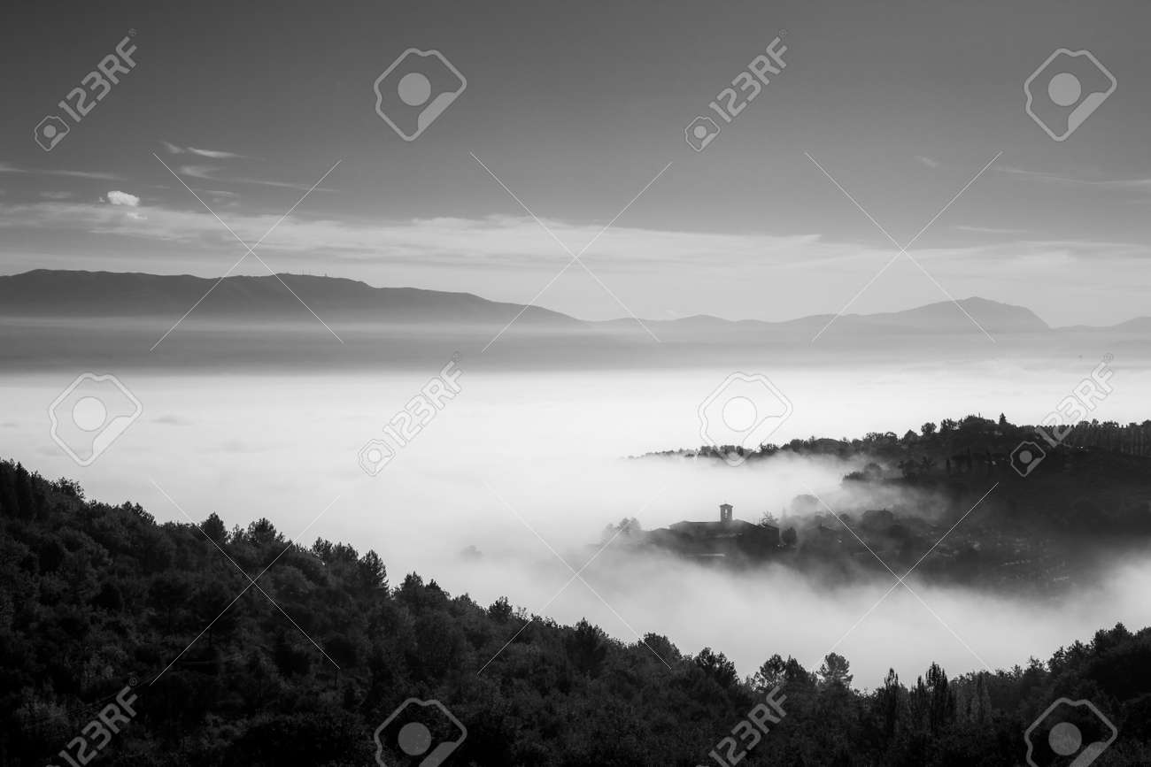 Surreal view of of a little town in Umbria (Italy) almost completely hidden by fog. - 145050329