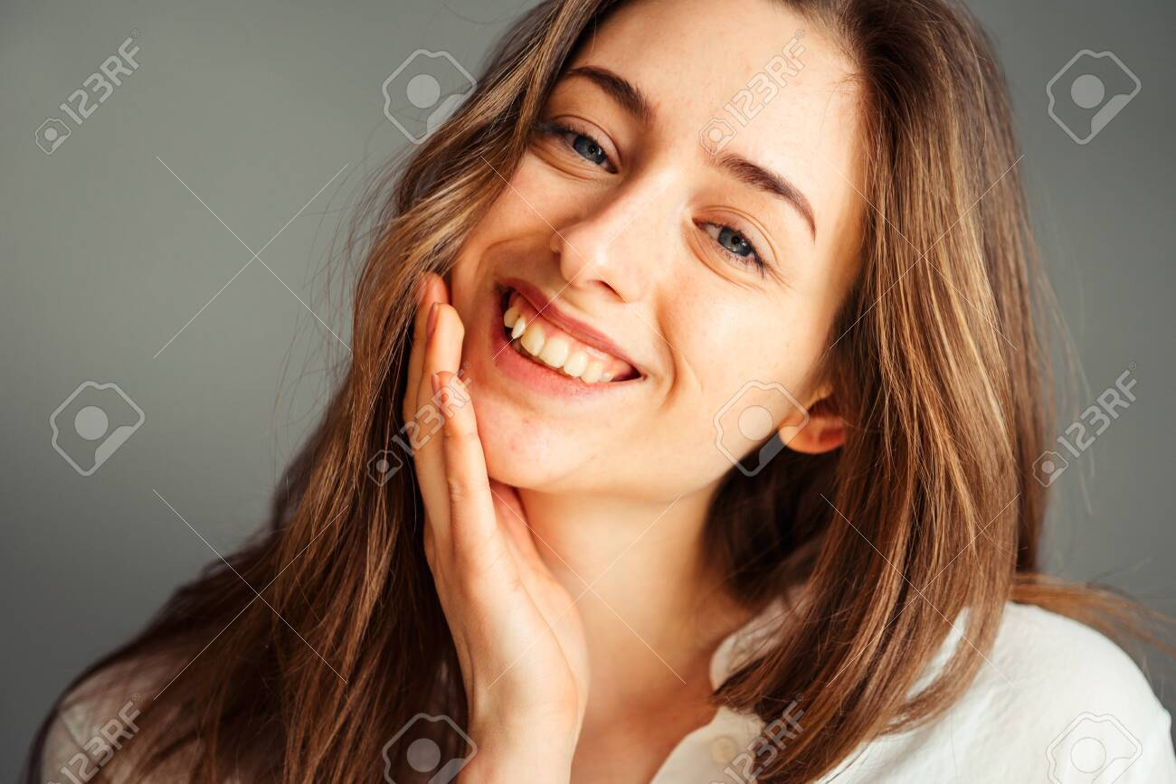 Close-up portrait of a smiling young girl in a white shirt on a gray background. Hands near the face. without retouching and makeup. - 148923376