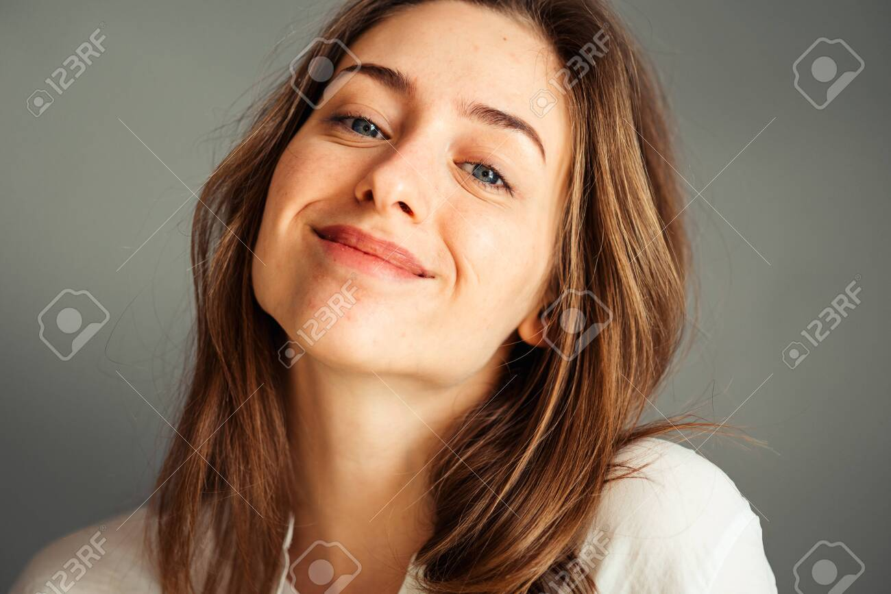 Close-up portrait of a smiling young girl in a white shirt on a gray background. Hands near the face. without retouching and makeup. - 148923377