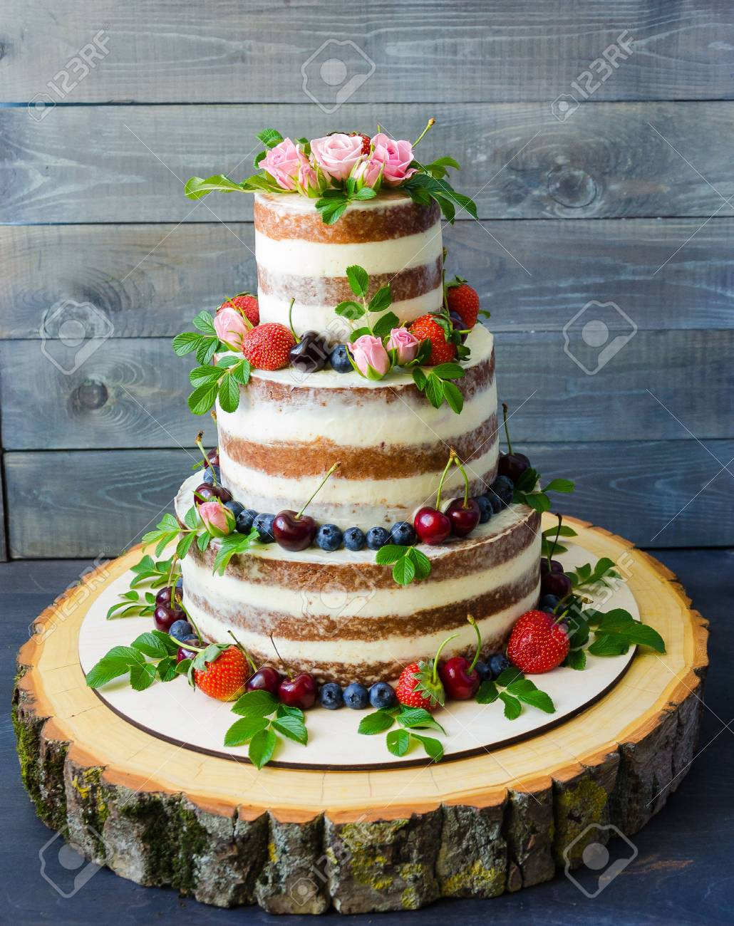 Naked Wedding Cake Decorated With Berries And Flowers Stock Photo