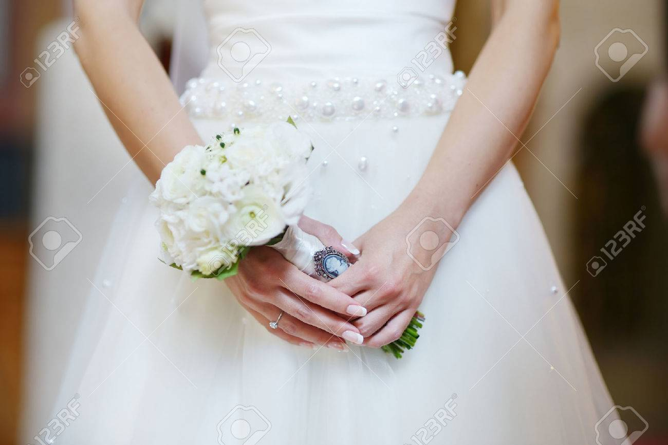 Bride holding flowers at the wedding ceremony in church - 39808948