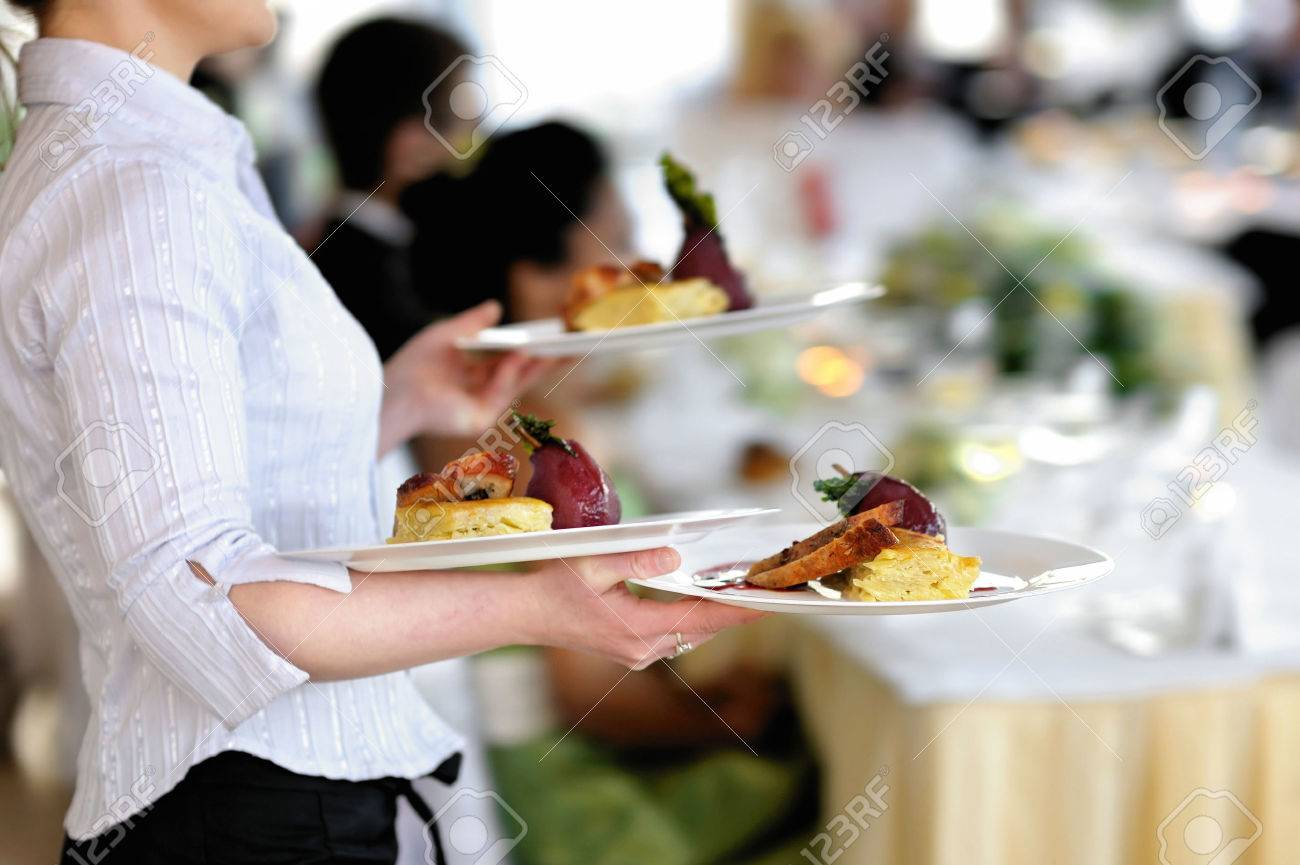 Waitress carrying three plates with meat dish - 40740643